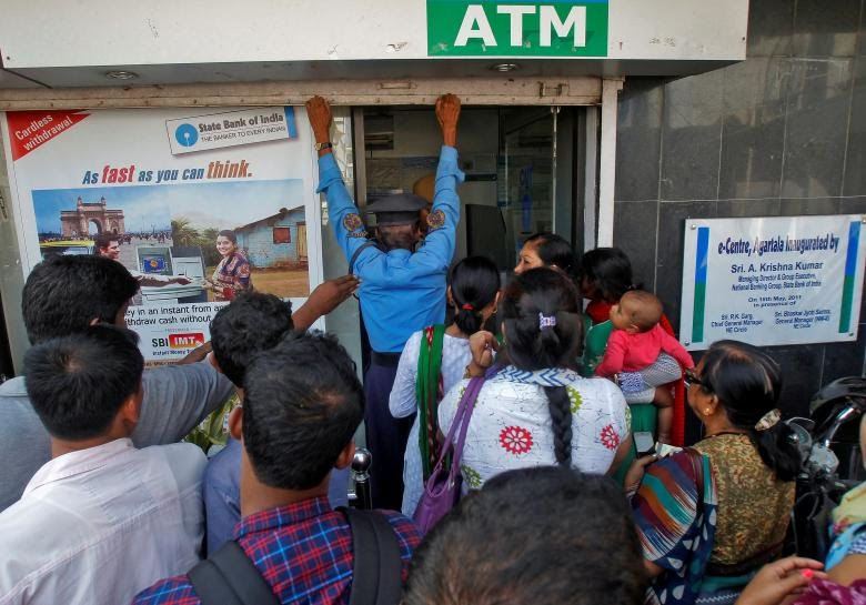 A security guard closes the shutter of State Bank of India ATM after it stopped dispensing cash in Agartala, India, November 15, 2016. Credit:Jayanta Dey/Reuters