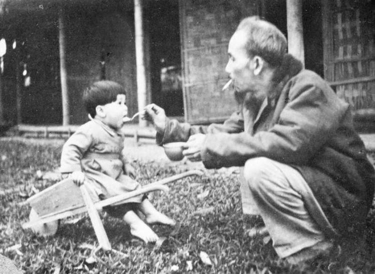 Chủ tịch Hồ Chí Minh bón cơm cho một cháu bé khi đến thăm trại nhi đồng ở chiến khu Việt Bắc (1950). (Ảnh: Tư liệu TTXVN)