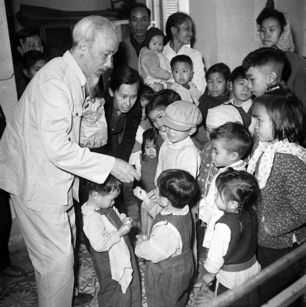 Chủ tịch Hồ Chí Minh thăm và chia kẹo cho các cháu nhi đồng ở nhà trẻ của con em công nhân nhà máy cao su Sao Vàng, xà phòng Hà Nội và thuốc lá Thăng Long, ngày 15/2/1961. (Ảnh: Tư liệu TTXVN)